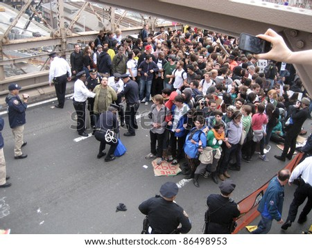 NEW YORK - October 1: A spectator snaps a camera phone picture as Occupy Wall Street protesters are arrested by police officers on the Brooklyn Bridge, October 1, 2011 in New York City. - stock photo
