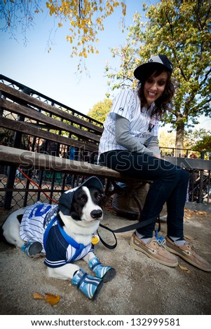 NEW YORK - OCTOBER 24, 2010: An unidentified young woman and her dog enjoy the annual Tompkins Square Halloween Dog Parade, wearing matching baseball player costumes. - stock photo