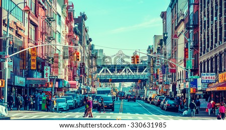 NEW YORK - OCTOBER 21, 2015: Busy street with crowded Chinese stores in Chinatown, Manhattan, New York. The neighborhood is home to the largest enclave of Chinese people in the Western Hemisphere. - stock photo