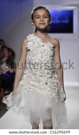 NEW YORK - OCTOBER 21: Girl walks runway petite Parade show by Mischka Aoki during kids fashion week sponsored by Vogue Bambini & Swarovski Elements at Industria Supertudio on October 21, 2012 in NYC - stock photo