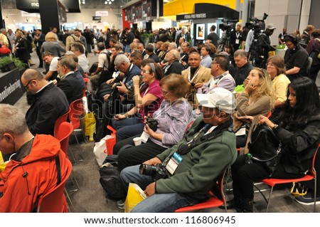 NEW YORK - OCTOBER 26: People visiting the PDN PhotoPlus Expo, the largest photography and imaging show in North America, was held at the Jacob K. Javits Convention Center on October 26, 2012 in NYC - stock photo