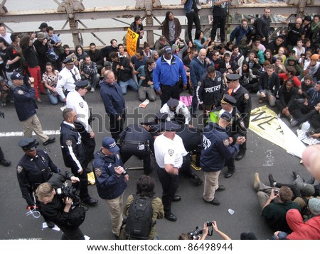 NEW YORK - October 1: Protesters are blocked by policy officers on the Brooklyn Bridge, October 1, 2011 in New York City. - stock photo