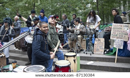 NEW YORK - OCTOBER 21: Smiling musicians join protesters with their drums in 'Occupy Wall Street' camp in Zuccotti Park in Downtown Manhattan on October 21, 2011 in New York.