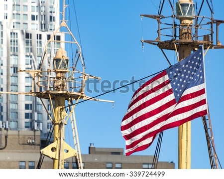 New York Port scenes: US Flag flying on the crow nest of a sail ship, against a clear blue sky. The crow nest has a beacon fixed in it. - stock photo