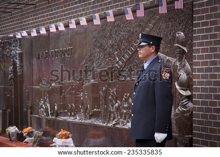 NEW YORK - SEPT 11, 2014: A firefighter stands guard at the Memorial Wall at FDNY Engine 10 Ladder 10 House on Liberty St . The firehouse is directly across from the WTC site.  - stock photo