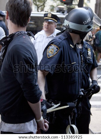 NEW YORK - SEPT 17: A policeman holds the on to a suspect after arresting the unidentified man on the 1yr anniversary of the Occupy Wall St protests on September 17, 2012 in New York City, NY. - stock photo