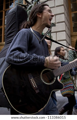 NEW YORK - SEPT 17:  A protester plays his guitar and sings while walking up Broadway during on the 1yr anniversary of the Occupy Wall St protests on September 17, 2012 in New York City, NY. - stock photo