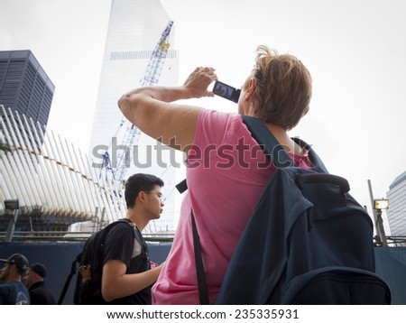 NEW YORK - SEPT 11, 2014: A tourist takes a picture of the Freedom Tower and structures at the WTC site on the anniversary of the 2001 September 11 terrorist attacks in Lower Manhattan. - stock photo