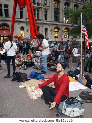 NEW YORK - SEPT.: A young man meditates amid the Occupy Wall Street demonstration near the New York Stock Exchange on September 21, 2011 in New York City. - stock photo