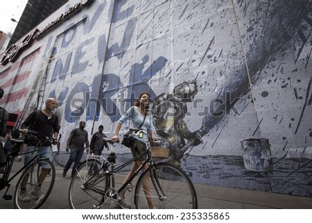 NEW YORK - SEPT 11, 2014: An unidentified couple walk their bikes by a mural that says We Love New York featuring a firefighter spraying water from a hose on the anniversary of the 2001 terror attack. - stock photo