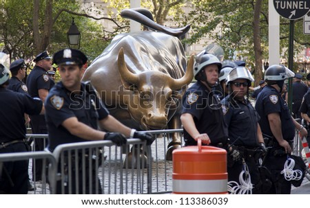 NEW YORK - SEPT 17: Police guard the bronze Charging Bull sculpture on Broadway in Bowling Green Park on the 1yr anniversary of the Occupy Wall St protests on September 17, 2012 in New York City, NY. - stock photo