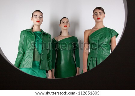 NEW YORK - SEPT 10: Three models standing behind a round window portal at the bebeBLACK Spring/Summer 2013 collection presentation during Mercedes-Benz Fashion Week in New York on September 10, 2012. - stock photo