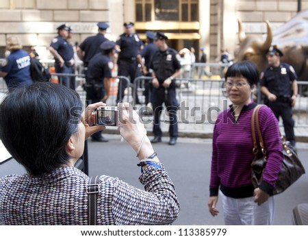 NEW YORK - SEPT 17: Tourists take pictures as police guard the Charging Bull sculpture  in Bowling Green on the 1yr anniversary of Occupy Wall St protests on September 17, 2012 in New York City, NY.