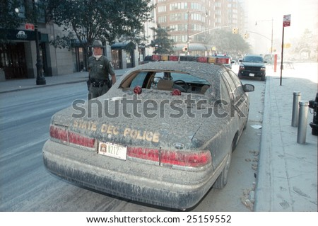 NEW YORK - SEPTEMBER 11:  A NY State Dept of Env. Cons. (DEC) officer stands near a damaged vehicle near Ground Zero after the collapse of the Twin Towers September 11, 2001 in New York City.