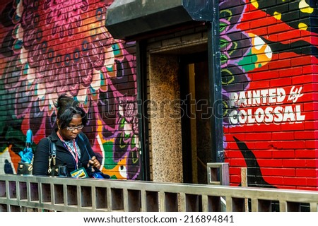 NEW YORK-SEPTEMBER 12-A woman enters a subway station hand painted by Colossal Media on September 12 2014 in New York City. - stock photo