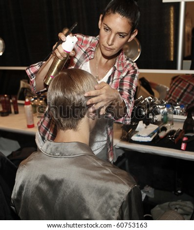 NEW YORK - SEPTEMBER 10: Hairstylist prepares model backstage for Duckie Brown Collection for Spring/Summer 2011 during Mercedes-Benz Fashion Week on September 10, 2010 in New York - stock photo
