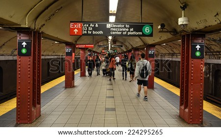 NEW YORK - SEPTEMBER 21, 2014: MTA subway train station platform with people traveling in New York. The NYC Subway is a rapid transit/transportation system in the City of NY. - stock photo