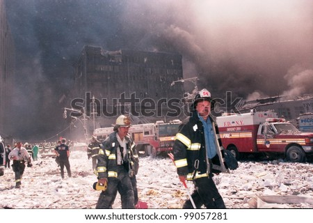 NEW YORK - SEPTEMBER 11: New York City firefighters walk near the area known as Ground Zero after the collapse of the Twin Towers on September 11, 2001 in New York City. - stock photo