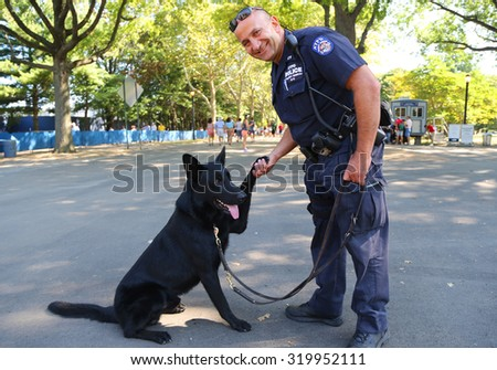 NEW YORK - SEPTEMBER 5, 2015: NYPD transit bureau K-9 police officer and German Shepherd K-9 providing security at National Tennis Center during US Open 2015 in New York - stock photo