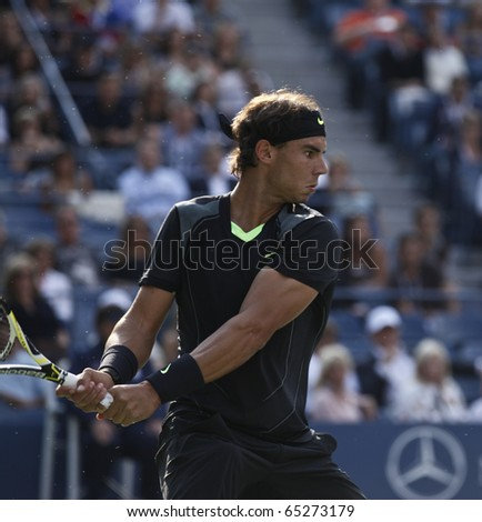 NEW YORK - SEPTEMBER 13: Rafael Nadal of Spain returns ball during final match of US Open Tennis Championship against Novak Djokovic of Serbia on September 13, 2010 in New York, City. - stock photo