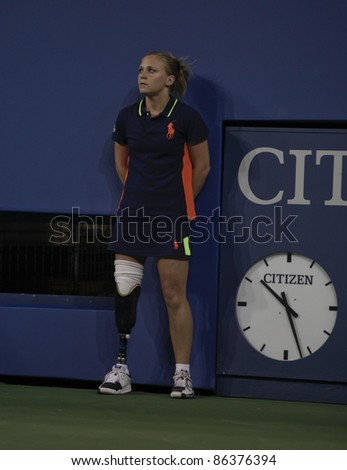 NEW YORK - SEPTEMBER 10: US Open ball person Denise Castelli of New Jersey with prosthetic leg works during match between Caroline Wozniacki of Denmark and Serena Williams of USA on Sep 10, 2011 in NYC - stock photo