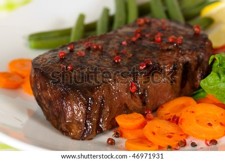 New York Steak- meat on Green Beans,Carrot,Pepper and green salad over plate - stock photo