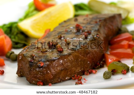 New York Steak- meat on Green Salad,Red Bell Pepper and Capers over plate - stock photo