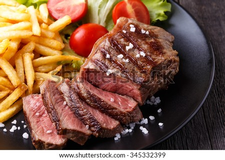 New York steak with french fries and salad.