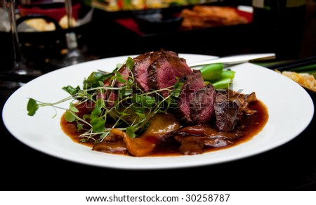 New York strip steak thinly sliced.  Medium-rare, with micro-greens in a cognac sauce. - stock photo