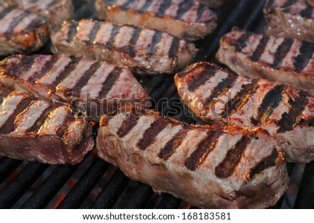 New York strip steaks on a charcoal grill.