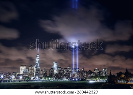 NEW YORK, UNITED STATES - SEPTEMBER 11: illuminated Manhattan skyline with two beams of light in memory of 9/11 over Hudson River, New York City on September 11, 2014 - stock photo
