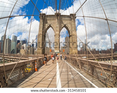 NEW YORK,USA - AUGUST 20,2015 : Tourists and locals crossing the Brooklyn Bridge on a beautiful summer day