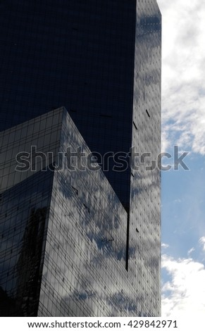 New York, USA. Glass skyscraper. Cloudy summer day. Warm weather. Summer in the city. Downtown building. Reflections of the sky.  - stock photo