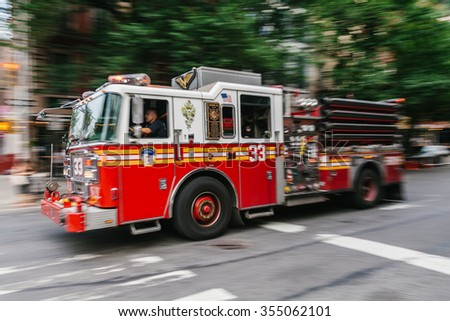 NEW YORK, USA - JULY 13, 2015: Firefighter truck on Manhattan streets. FDNY provide both Fire and EMS services on July 13, 2015 in New York, USA - stock photo