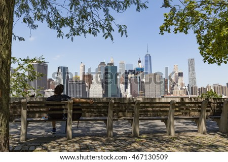 NEW YORK, USA - July 20, 2016: Manhattan skyline from Brooklyn Heights Promenade. Male relax and enjoy the stunning views of Manhattan