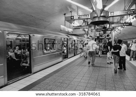 NEW YORK, USA - JULY 3, 2013: People board train at Grand Central Terminal subway station in New York. With 1.67 billion annual rides, New York City Subway is the 7th busiest metro system in the world - stock photo