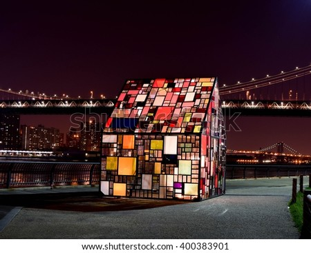 NEW YORK, USA - JULY 11, 2015: The stained glass house called the Kolonihavehus is seen in Brooklyn Bridge Park. This colorful house is a work of art done by artist Tom Fruin. - stock photo