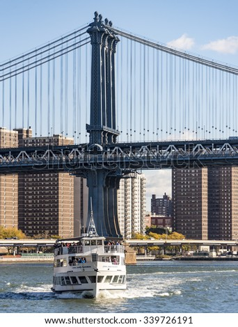 NEW YORK,USA-JULY 3,2015:Tourism in New York: Sightseeing cruise near the Manhattan Bridge on East River.The Brooklyn Bridge is a hybrid cable-stayed or suspension bridge in New York City. - stock photo