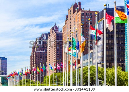 NEW YORK, USA - JULY 12, 2015: United Nations Headquarters with flags of the members of the UN in New York.  The complex has served as the official headquarters of the UN since  1952. - stock photo