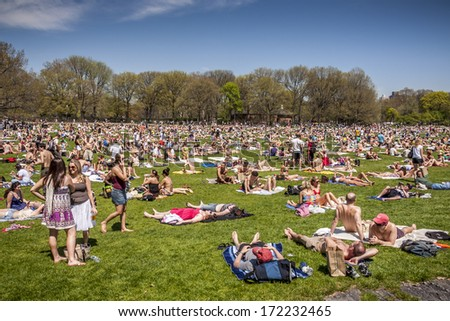 NEW YORK, USA - JUNE 10, 2013:  Locals and tourists crowded the Central Park in New York city, USA to enjoy the nice weather and take a sunbath after a very harsh winter season on June 10, 2013. - stock photo