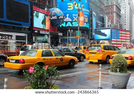 NEW YORK, USA - JUNE 10, 2013: Taxis drive in rain in Times Square, NY. Times Square is one of most recognized places in the world. More than 300,000 people pass through Times Square daily. - stock photo