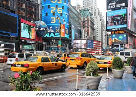 NEW YORK, USA - JUNE 10, 2013: Taxis drive in rainy Times Square, NY. Times Square is one of most recognized places in the world. More than 300,000 people pass through Times Square daily.