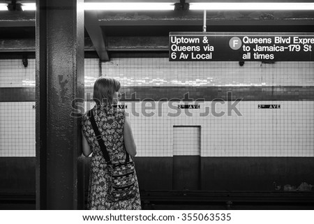 NEW YORK, USA - JUNE 13, 2015: Woman waiting the train in the New York Subway, the largest rapid transit system in the world with 469 stations, on June 13, 2015 in New York, USA - stock photo