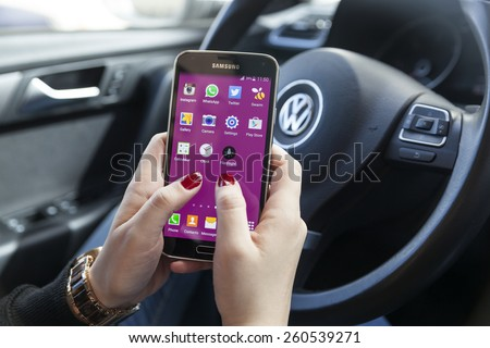 New York, USA - March 08, 2015: Woman using her black Samsung S5 smart phone in the car. - stock photo