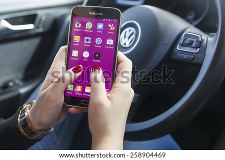 New York, USA - March 08, 2015: Woman using her black Samsung S5 smart phone phone in the car. - stock photo