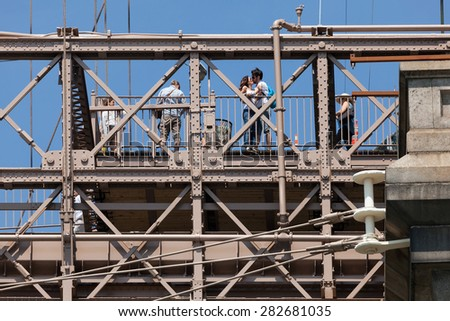 NEW YORK, USA - MAY 25 2015: The Brooklyn Bridge, one of the oldest bridges in US, has a wide pedestrian walkway open to walkers and cyclists, attracting large crowds of tourists. - stock photo