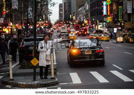 NEW YORK, USA - Sep 20, 2016: Manhattan street scene. Woman waits for a taxi on the streets of New York City in evening time