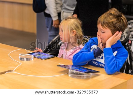 NEW YORK, USA - SEP 22, 2015: Unidentified children in the Apple store on the Fifth Avenue, New York. The store sells Macintosh personal computers, software, iPod, iPad, iPhone, Apple Watch, Apple TV - stock photo