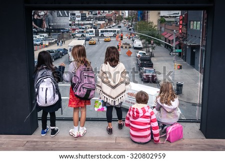 NEW YORK, USA - SEPTEMBER 30, 2009: Children looking at traffic on 10th avenue from Highline, Manhattan, New York, USA. Highline is famous historical sightseeing in New York. - stock photo