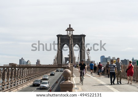 New York, USA - September 21, 2015:  People and cars on the Brooklyn bridge in New York.